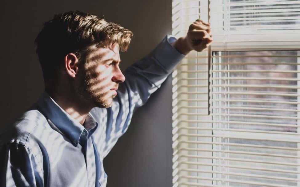 uomo che guarda fuori dalla finestra