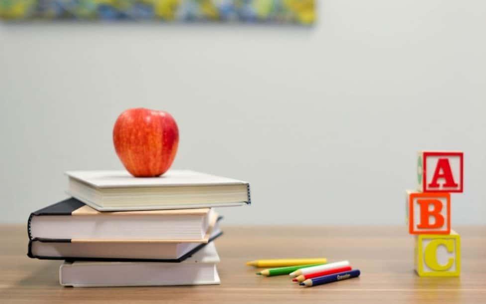 mela sui libri con matite